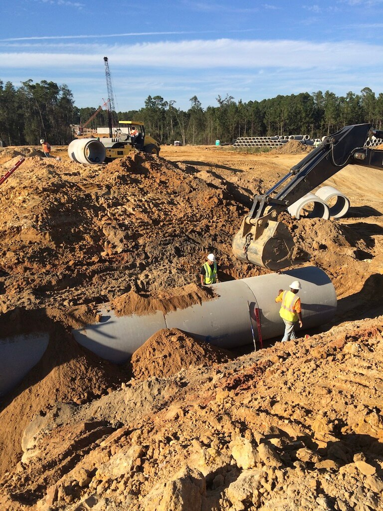 GEC employees installing an underground concrete pipe